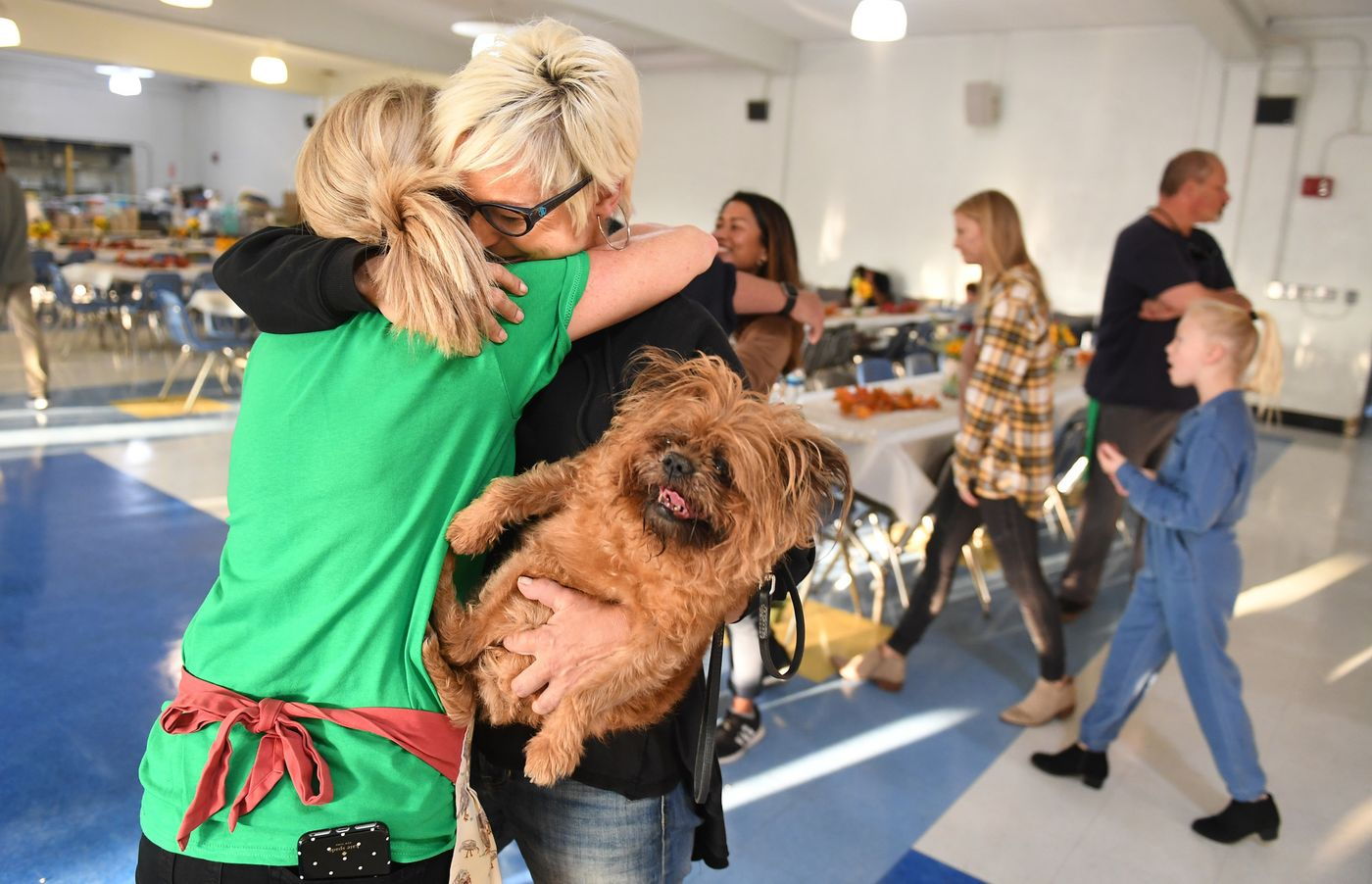 "Robin Levy, whose home burned down in Malibu, holds her dog Violet while being hugged by friend Yvette Kleiser at a ""Happy Friendsgiving"" at Santa Monica High School on Nov. 20, 2018. (Credit: Wally Skalij / Los Angeles Times)"