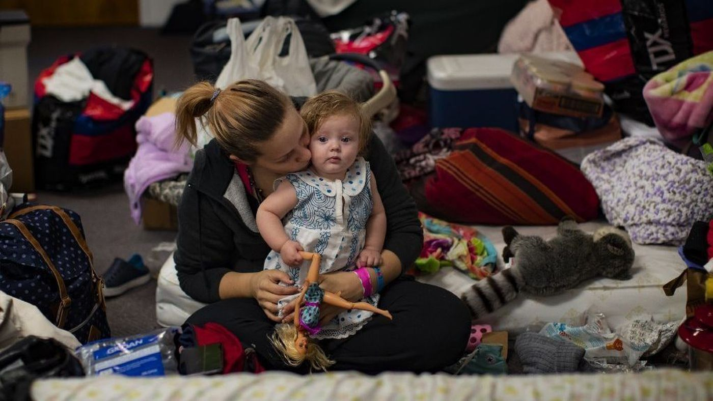 Jessica Swisher kisses her 7-month-old daughter, Ryan Busby, surrounded by their belongings at a church shelter in Chico where she is staying with her husband and three other daughters after escaping the Camp fire. (Credit: Gina Ferazzi / Los AngelesTimes)