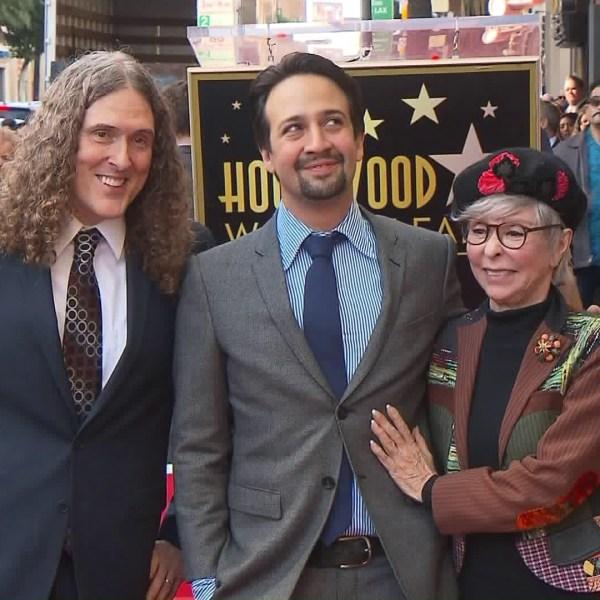 Lin-Manuel Miranda, center, stands alongside Weird Al Yankovic and Rita Moreno while receiving a star on the Hollywood Walk of Fame on Nov. 30, 2018. (Credit: KTLA)