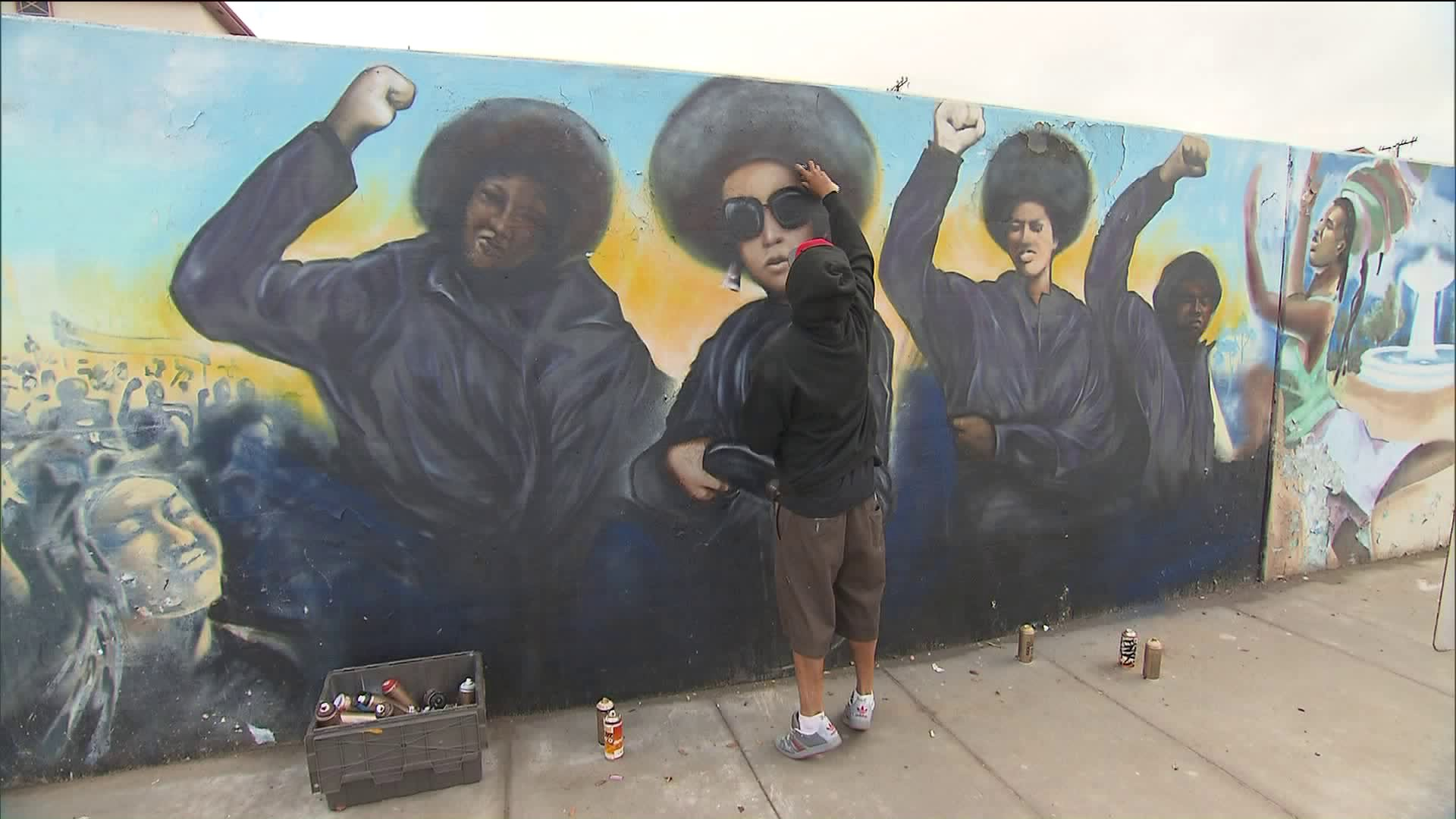 """Artist Enkone works to cover up swastikas painted on the """"Our Mighty Contribution"""" mural at Crenshaw Boulevard and 50th Street in the Hyde Park neighborhood of Los Angeles on Nov. 29, 2018. (Credit: CNN)"""