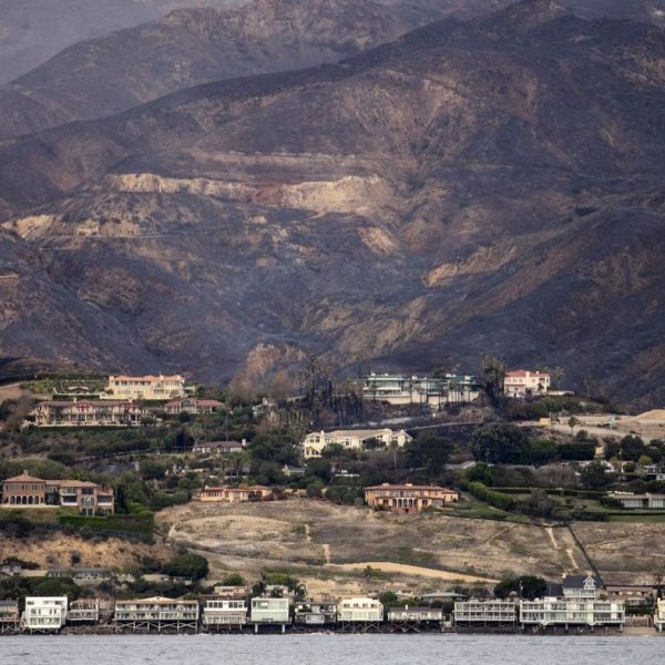 The charred Santa Monica Mountains rise behind homes in Malibu along Pacific Coast Highway, seen from a yacht that was bringing supplies to Paradise Cove on Nov. 13, 2018. (Credit: Jay L. Clendenin / Los Angeles Times)