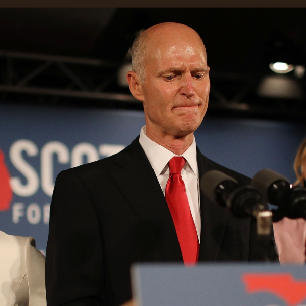 Florida Gov. Rick Scott pauses as he becomes emotional while speaking as he stands with his wife, Ann Scott, left, and daughter Alison Guimard, right, during his election night party at the LaPlaya Beach & Golf Resort on Nov. 6, 2018 in Naples, Florida. (Credit: Joe Raedle/Getty Images)