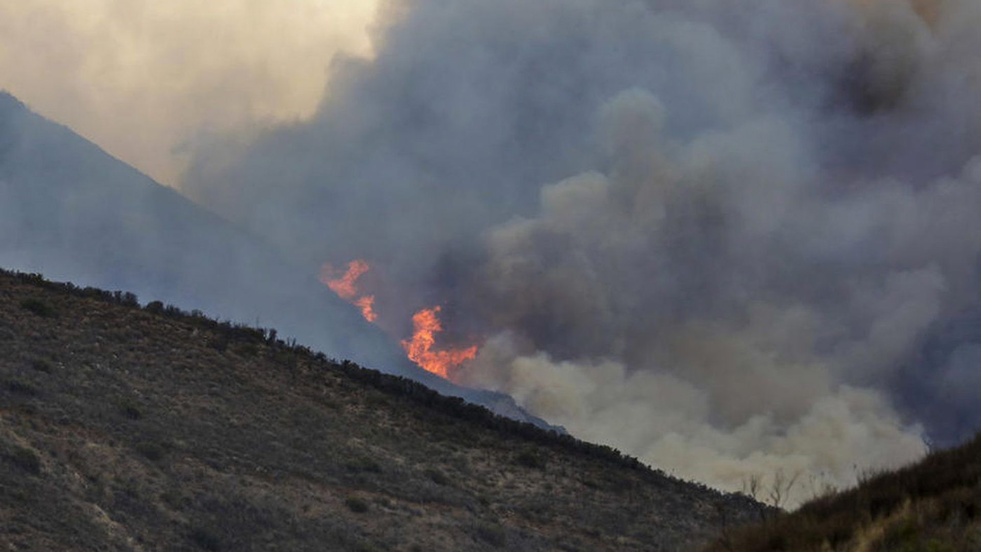 Planes and helicopters battle a fire burning on Boney Mountain in Point Mugu State Park. (Credit: Irfan Khan / Los Angeles Times)