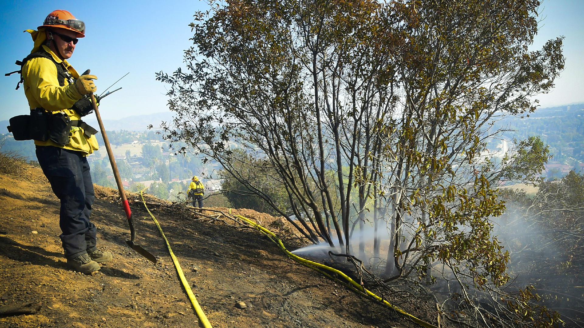 A firefighter overlooks the scene standing beside a a punctured hose spraying out water on a hillside overlooking homes in West Hills, near Malibu, California on November 11, 2018, as the battle to control the Woolsey Fire continues. (Credit: FREDERIC J. BROWN/AFP/Getty Images)