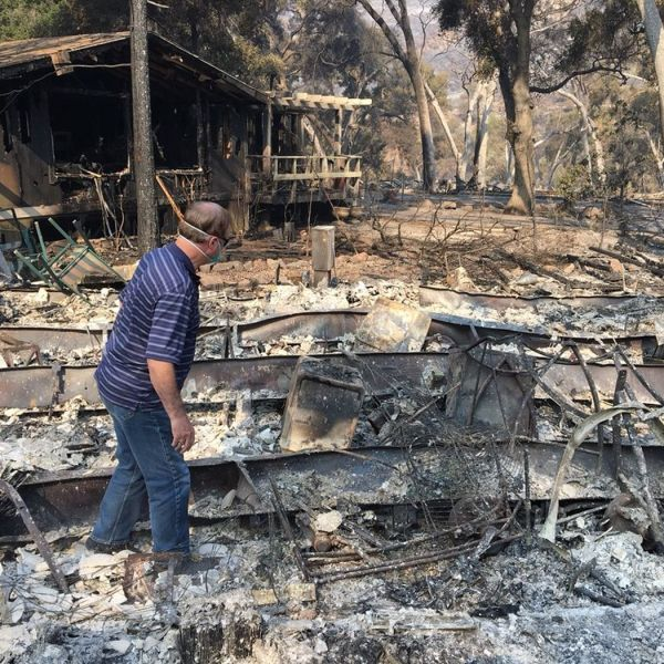 David Spence inspects the burned-out shell of his home in Oak Forest Estates. (Credit: Dakota Smith / Los Angeles Times)