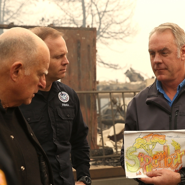 Gov. Jerry Brown and FEMA Administrator Brock Long look on as U.S. Secretary of the Interior Ryan Zinke holds up a child's school work as they tour a school burned by the Camp Fire on Nov. 14, 2018, in Paradise. (Credit: Justin Sullivan/Getty Images)