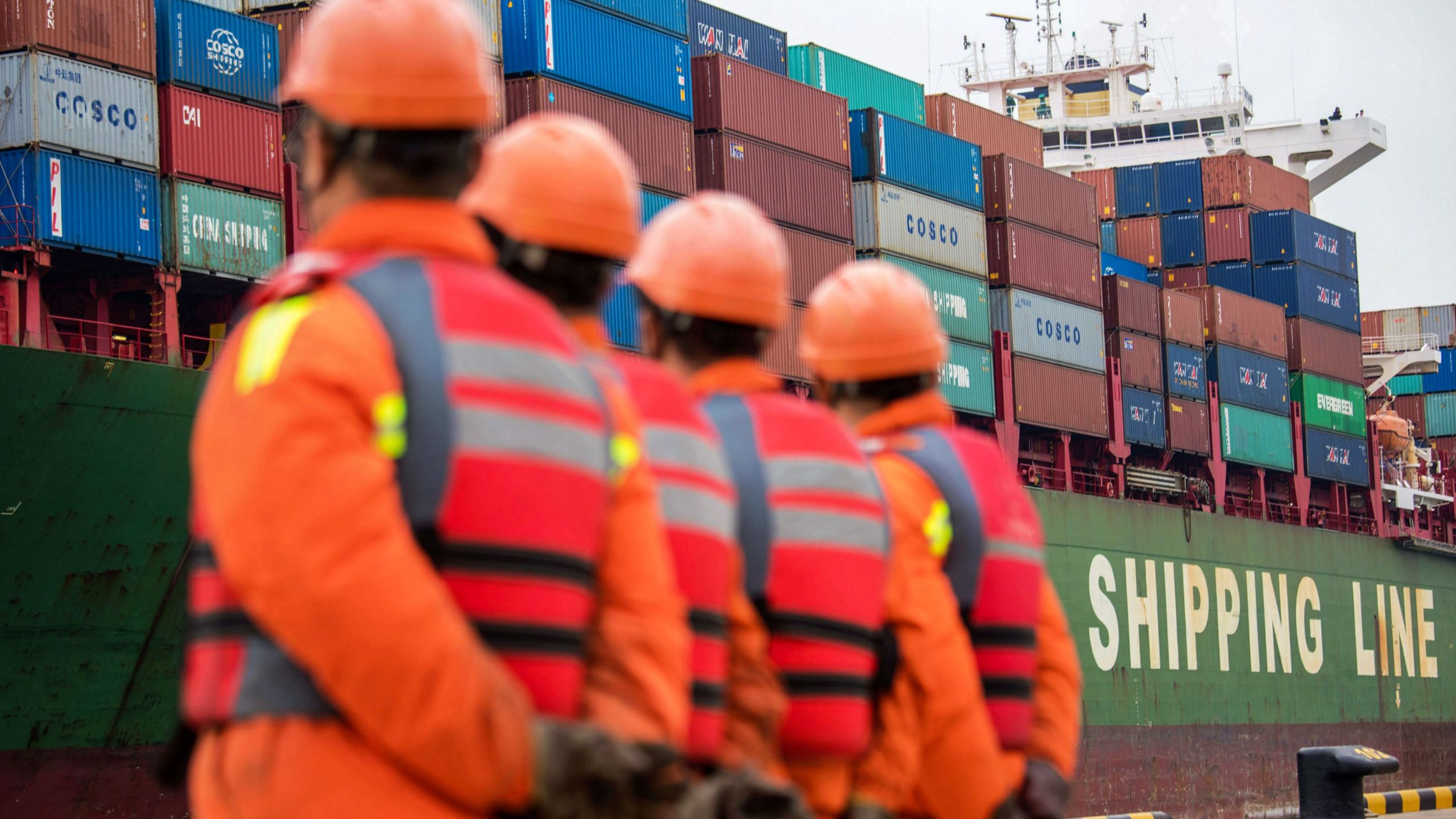 Employees look at a cargo ship at a port in Qingdao, east China's Shandong province on Nov. 8, 2018. (Credit: STR/AFP/Getty Images)