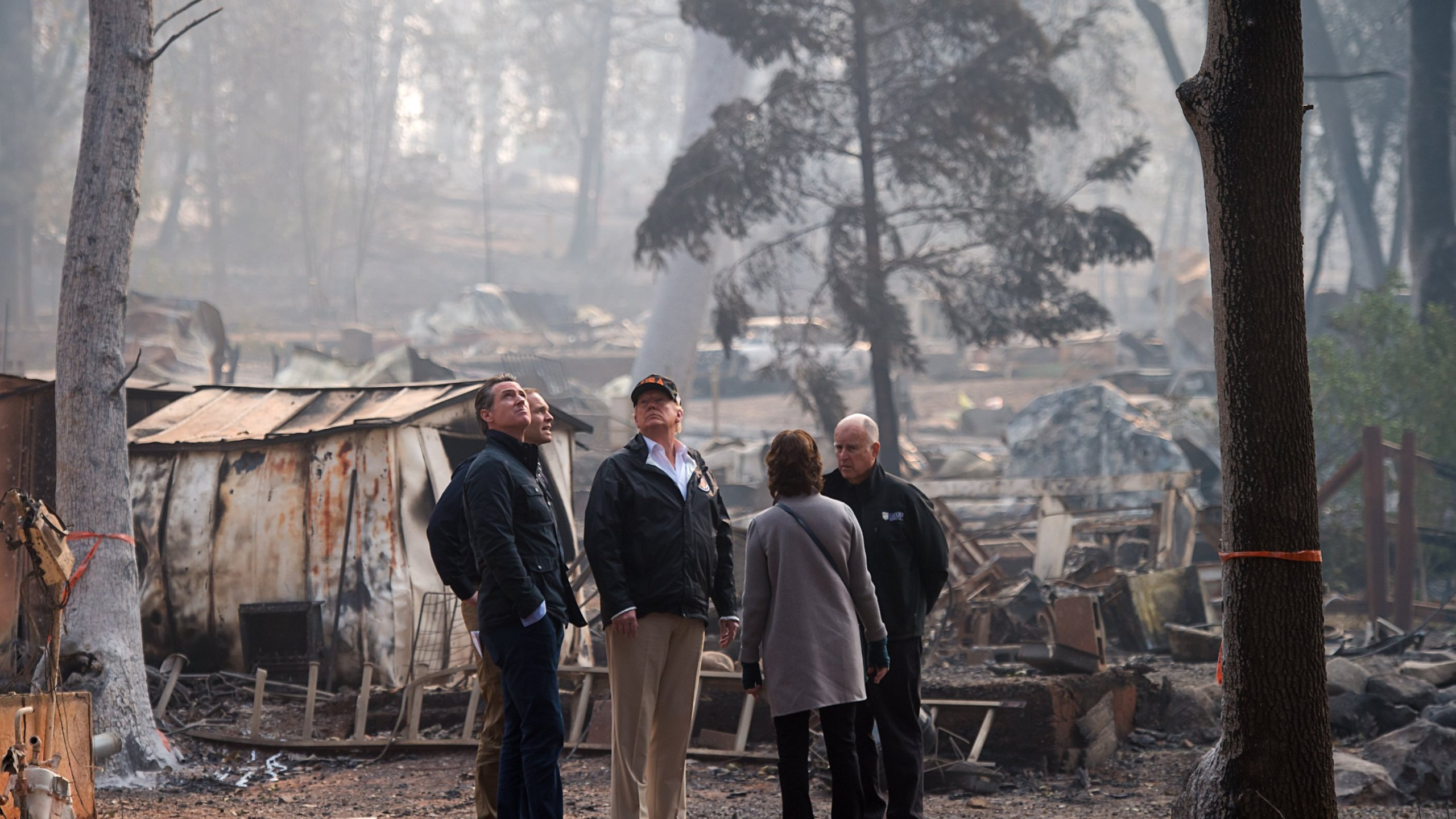 Gavin Newson, FEMA Director Brock Long, Donald Trump, Paradise mayor Jody Jones and Gov. Jerry Brown tour the Skyway Villa Mobile Home and RV Park, during Trump's visit of the Camp Fire in Paradise on Nov. 17, 2018. (Getty: Paul Kitagaki Jr.-Pool/Getty Images)