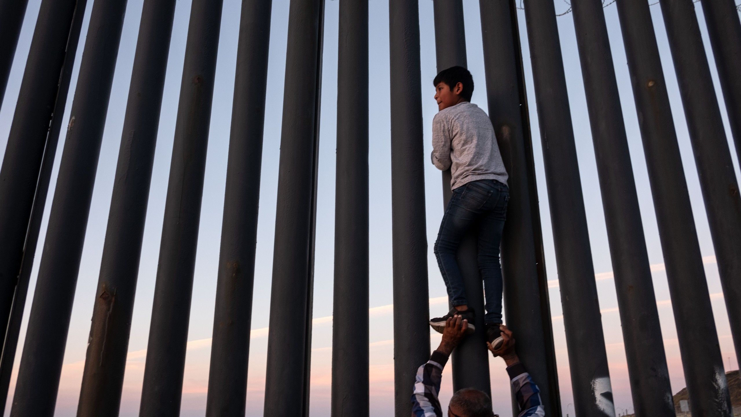 A man helps a boy to have a better look at the US-Mexico border wall in Playas de Tijuana, northwestern Mexico, November 18, 2018. (Credit: GUILLERMO ARIAS/AFP/Getty Images)