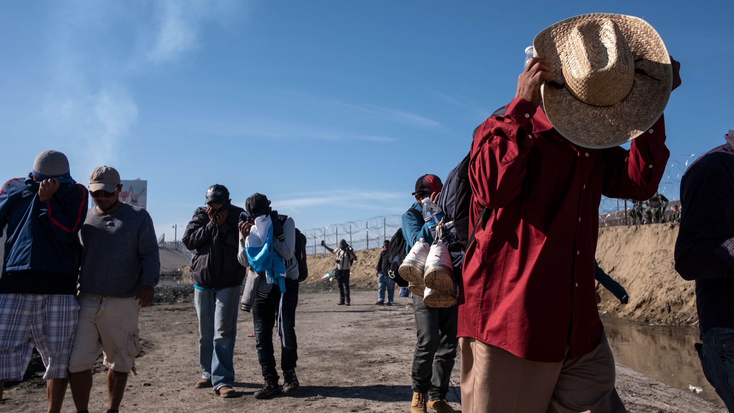 Central American migrants cover their faces next to the Tijuana River near the El Chaparral border crossing in Tijuana, Mexico, after the U.S. Border Patrol threw tear gas to disperse them after an alleged verbal dispute on Nov. 25, 2018. (Credit: Guillermo Arias / AFP / Getty Images)