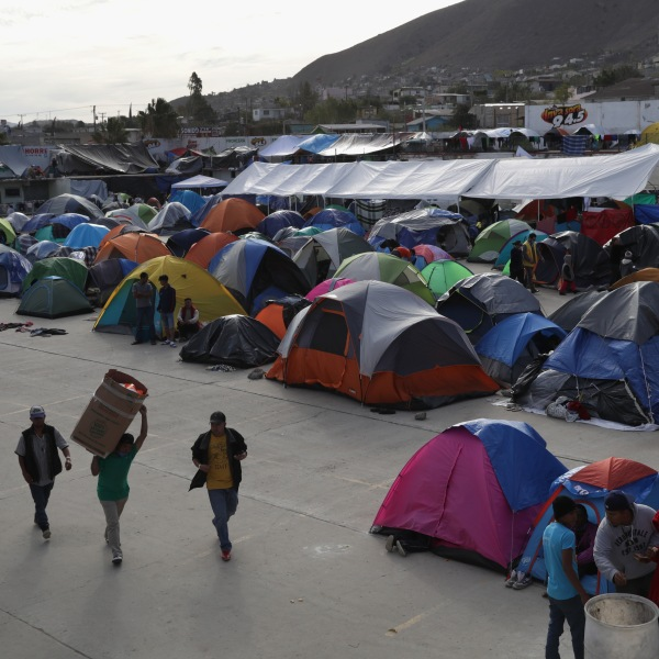 Immigrants spend the afternoon inside the Barretal migrant camp on Dec. 4, 2018 from Tijuana, Mexico. After traveling more than 6 weeks from Central America, thousands of immigrants from the migrant caravan remain in Tijuana, many awaiting asylum interviews and others deciding whether to cross illegally into the United States. (Credit: John Moore/Getty Images)