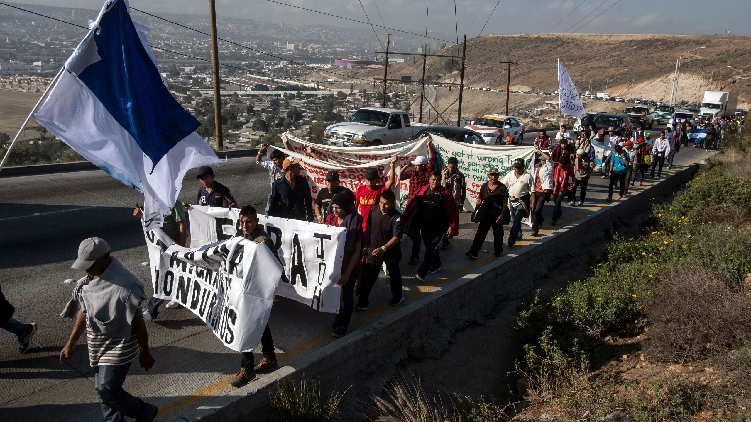 A group of Central American migrants take part in a demonstration march heading to the US Consulate to deliver a petition, in Tijuana, Baja California state, Mexico on December 11, 2018. - (Credit: GUILLERMO ARIAS/AFP/Getty Images)