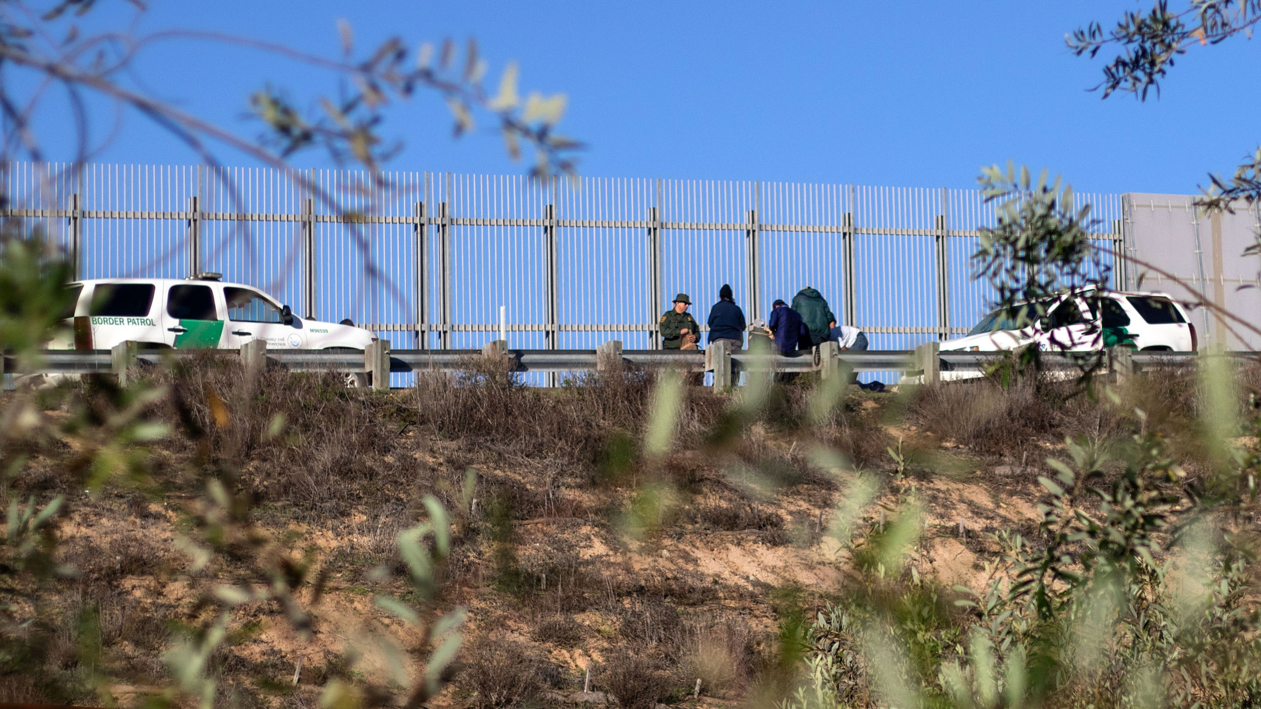 A group of migrants traveling in the Central American caravan are taken in custody by the U.S. Border Patrol after crossing the border fence into San Diego County, as seen from Playas de Tijuana, Mexico, on Dec. 12, 2018. (Credit: Guillermo Arias / AFP / Getty Images)