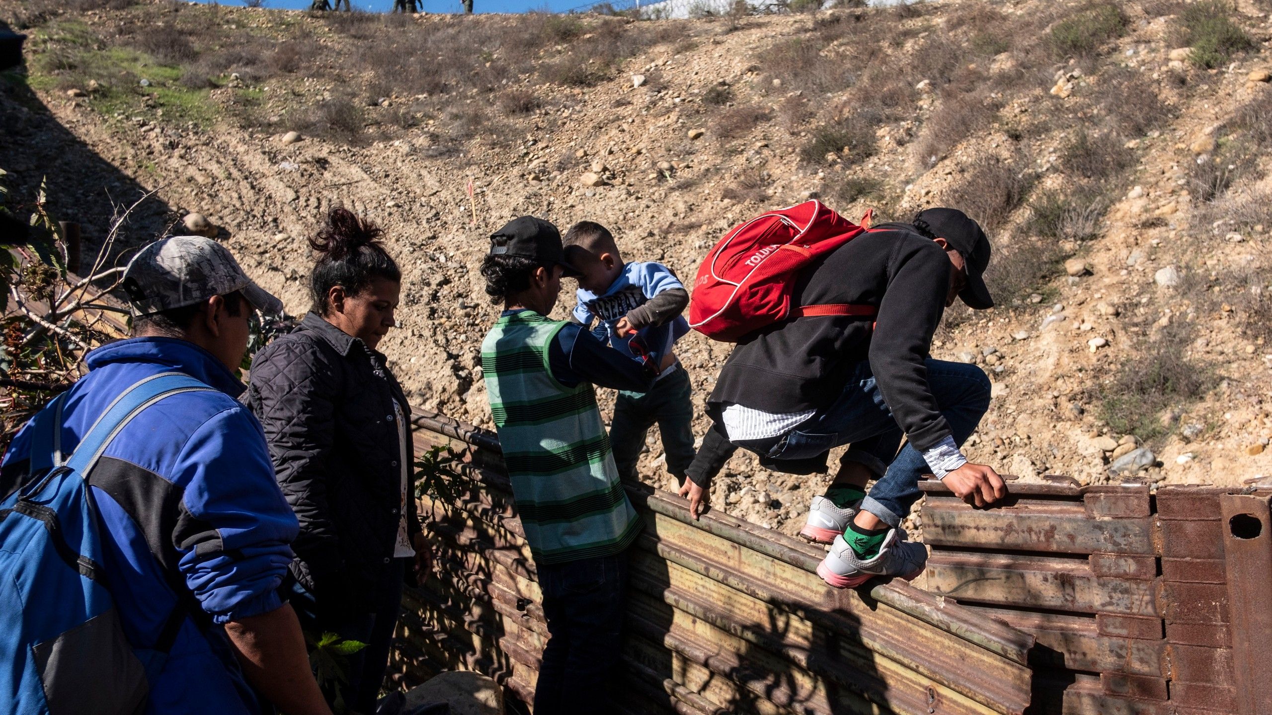 A group of Central American migrants -traveling in a caravan- cross the Mexico-US border fence to San Diego County, from Tijuana, on Dec. 16, 2018. (Credit: Guillermo Arias/AFP/Getty Images)