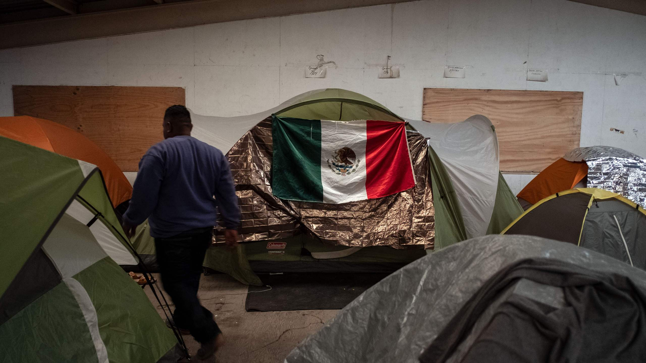 A Central American migrant who travelled in a caravan to the Mexico-U.S. border walks between tents at a temporary shelter in downtown Tijuana on Dec. 17, 2018. (Credit: Guillermo Arias / AFP / Getty Images)
