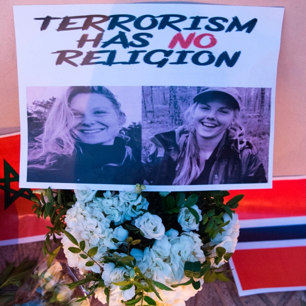 This picture taken on Dec. 21, 2018 shows photos of murdered Danish student Louisa Vesterager Jespersen on the Left and Nowegian Maren Ueland on the right, placed on top of flowers and between the flags of Morocco an Norway as Moroccans pay tribute to the Scandinavian victims. (Credit: Fadel Senna/AFP/Getty Images)