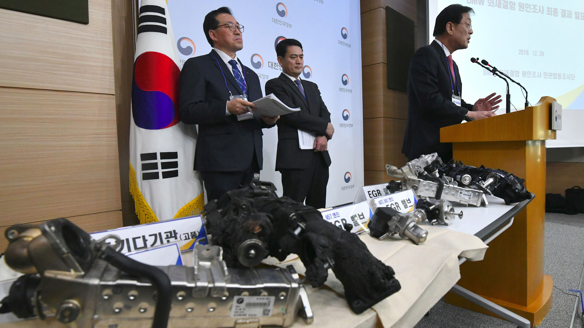 Parts of a burnt BMW car are displayed on a table during a press conference announcing the result of a five-month joint probe into BMW car engine fires, held at the South Korean government complex in Seoul on Dec. 24, 2018. (Credit: Jung Yeon-Je/AFP/Getty Images)