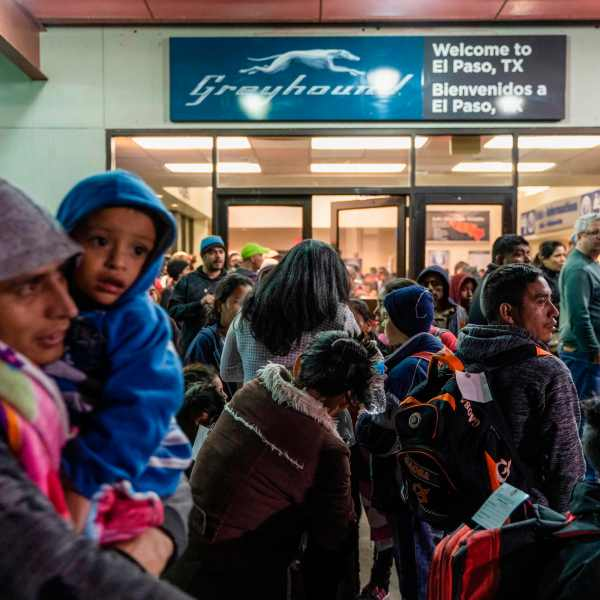 Asylum seekers stand at a bus stop after they were dropped off by Immigration and Customs Enforcement (ICE) at the Greyhound bus station in downtown El Paso, Texas late on Dec. 23, 2018. (Credit: PAUL RATJE/AFP/Getty Images)