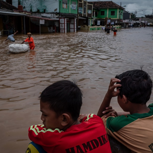 Children sit bey the flooded waters in an area hit by the effects of the tsunami on December 26, 2018 in Carita, Banten province, Indonesia. (Credit: Ulet Ifansasti/Getty Images)
