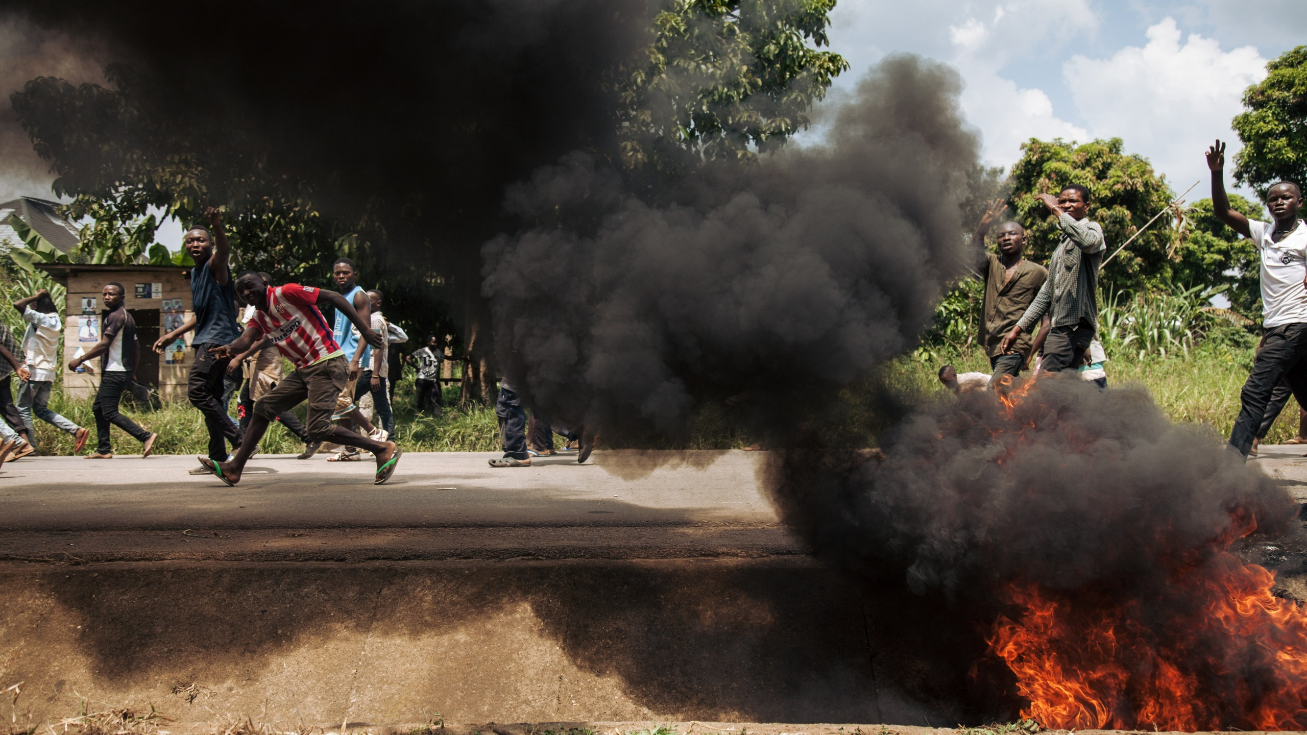 Protesters walk near the electoral commission in Beni during a demonstration against the postponement of elections in the territory of the Beni and the city of Butembo on Dec. 27, 2018. (Credit: ALEXIS HUGUET/AFP/Getty Images)