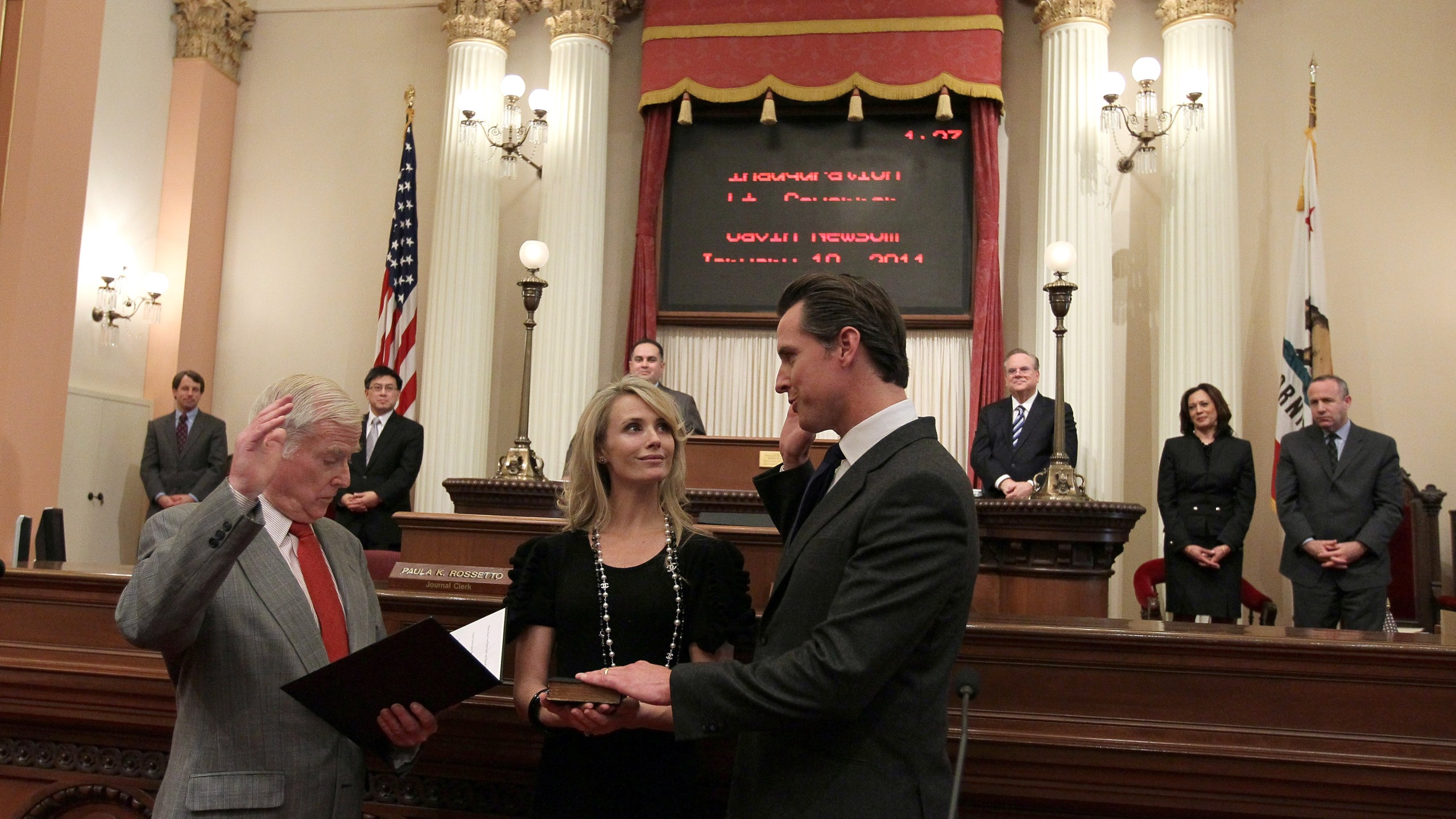Gavin Newsom, at right, is sworn in as the 49th lieutenant governor of California by his father William A. Newsom, left, as Gavin's wife Jennifer Siebel-Newsom, center, looks on at the California State Capitol in Sacramento on Jan. 10, 2011. (Credit: Justin Sullivan / Getty Images)