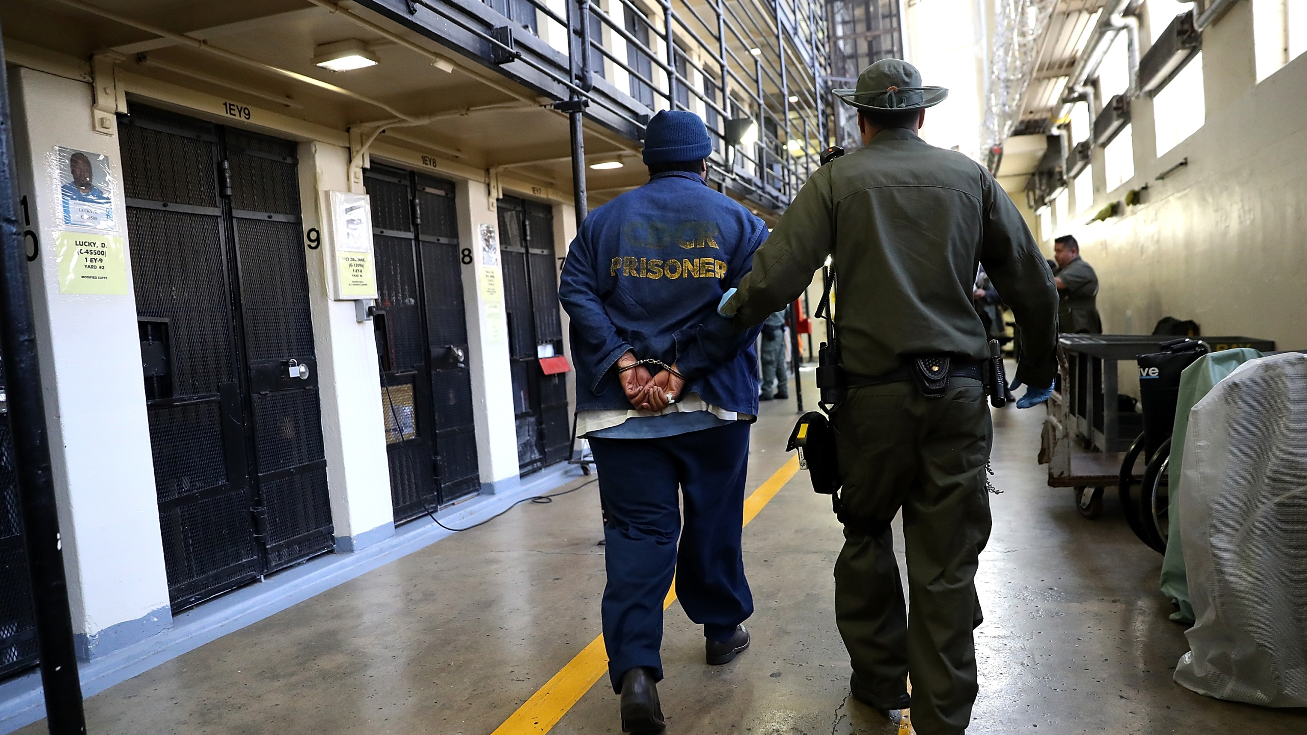 An armed California Department of Corrections and Rehabilitation officer escorts a condemned inmate at San Quentin State Prison's death row on Aug. 15, 2016. (Credit: Justin Sullivan / Getty Images)