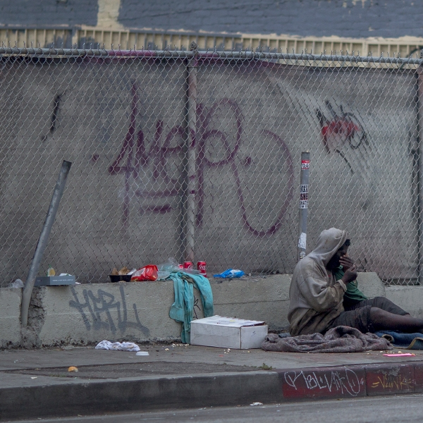 A homeless man sits on a downtown sidewalk where he had slept on May 1, 2017 in Los Angeles, California. (Credit: David McNew/Getty Images)