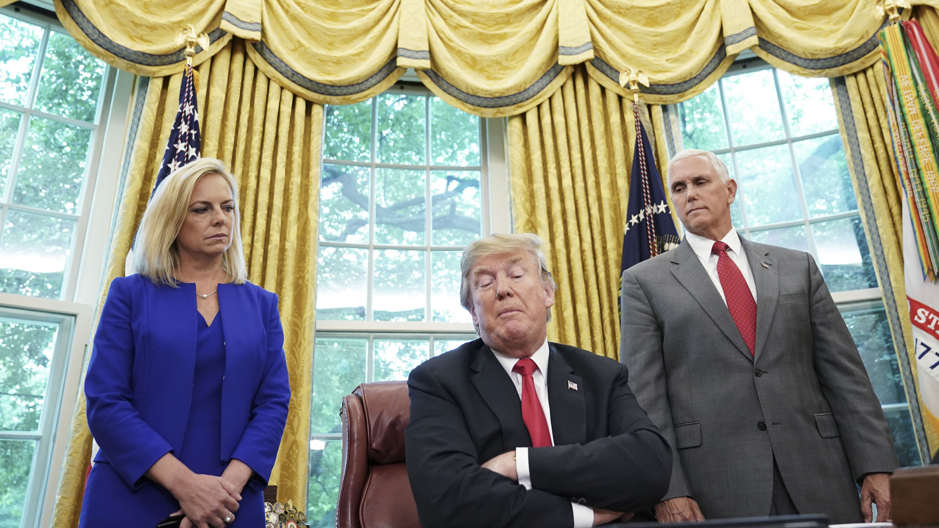 """Watched by Homeland Security Secretary Kirstjen Nielsen (L) and Vice President Mike Pence, US President Donald Trump signs an executive order on immigration in the Oval Office of the White House on June 20, 2018 in Washington, DC. - US President Donald Trump on Wednesday signed an executive order aimed at putting an end to the controversial separation of migrant families at the border, reversing a harsh practice that had earned international scorn.""""It's about keeping families together,"""" Trump said at the signing ceremony. """"I did not like the sight of families being separated,"""" he added. (Photo by Mandel Ngan / AFP) (Photo credit should read MANDEL NGAN/AFP/Getty Images)"""