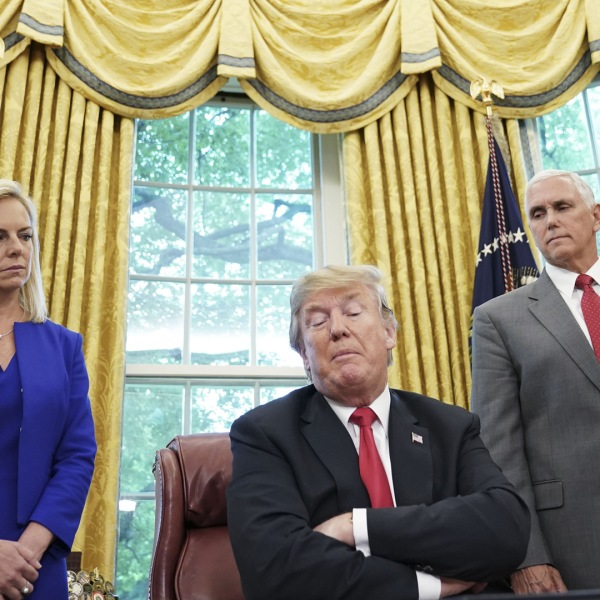 "Watched by Homeland Security Secretary Kirstjen Nielsen (L) and Vice President Mike Pence, US President Donald Trump signs an executive order on immigration in the Oval Office of the White House on June 20, 2018 in Washington, DC. - US President Donald Trump on Wednesday signed an executive order aimed at putting an end to the controversial separation of migrant families at the border, reversing a harsh practice that had earned international scorn.""It's about keeping families together,"" Trump said at the signing ceremony. ""I did not like the sight of families being separated,"" he added. (Photo by Mandel Ngan / AFP) (Photo credit should read MANDEL NGAN/AFP/Getty Images)"