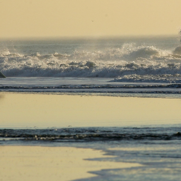 A surfer walks out into the water at Ocean Beach in San Francisco on Dec. 5, 2006. (Credit: Justin Sullivan/Getty Images)