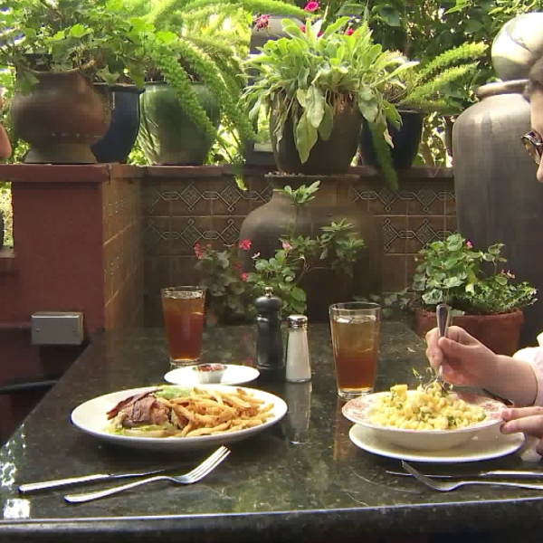 Chris Burrous dines with Rose Queen Louise Deser Siskel at La Grande Orange Cafe in Pasadena for a Burrous' Bites segment that aired on Dec. 30, 2018. (Credit: KTLA)