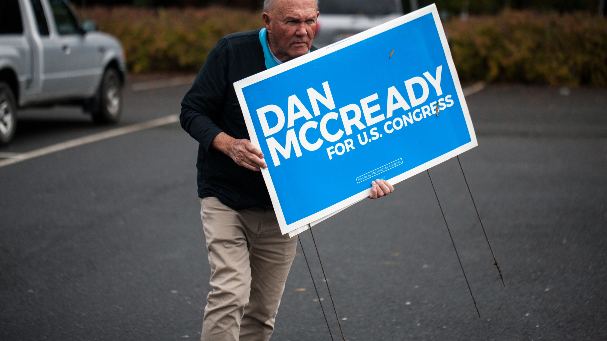 A campaign volunteer for Democratic House candidate Dan McCready carries signs on Nov. 6, 2018, in Charlotte, North Carolina. (Credit: Logan Cyrus / AFP / Getty Images)