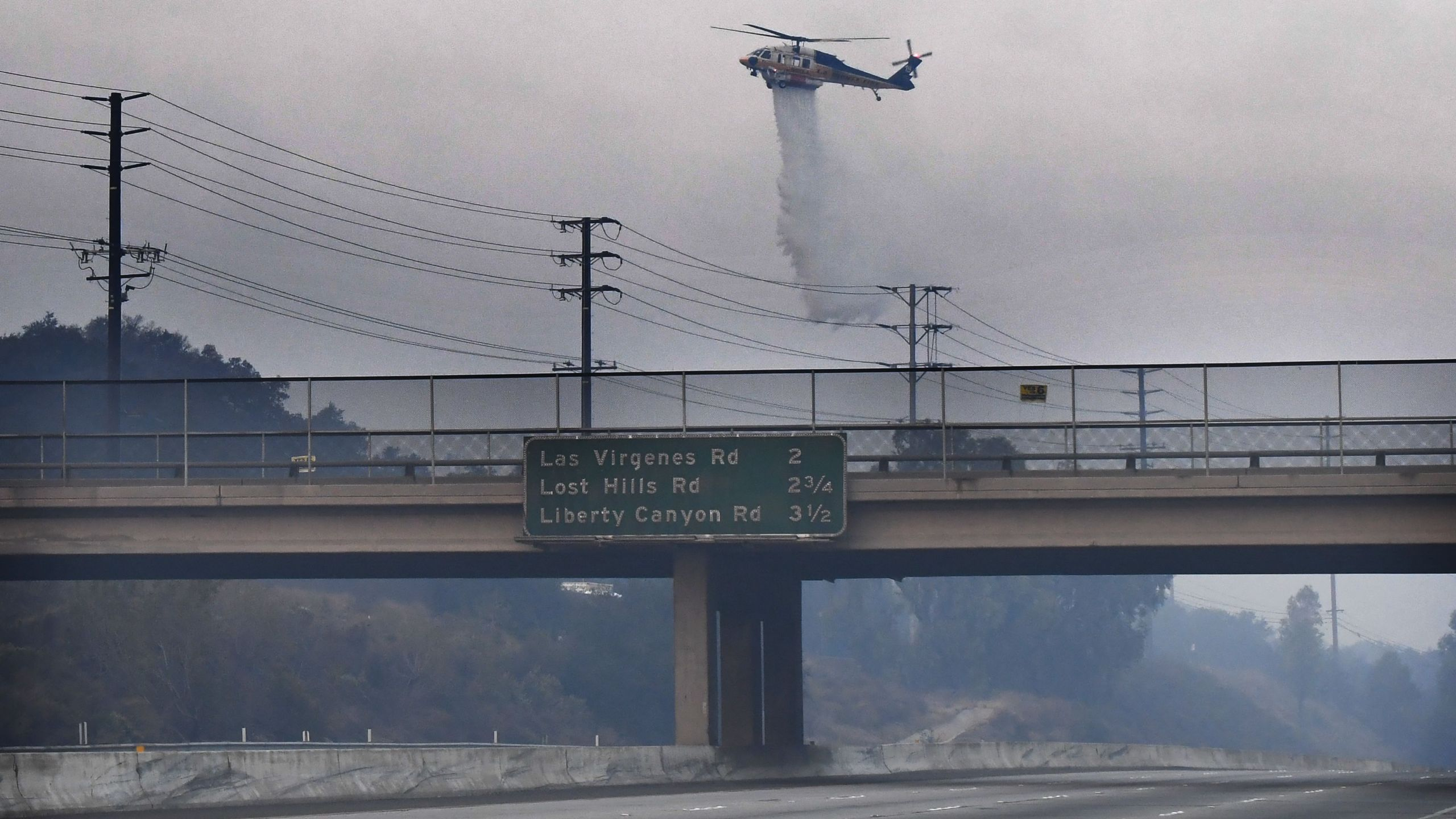 A helicopter drops water on a hot spot from the Woolsey Fire on Nov. 10, 2018 along the 101 Freeway in Calabasas. (Credit: ROBYN BECK/AFP/Getty Images)