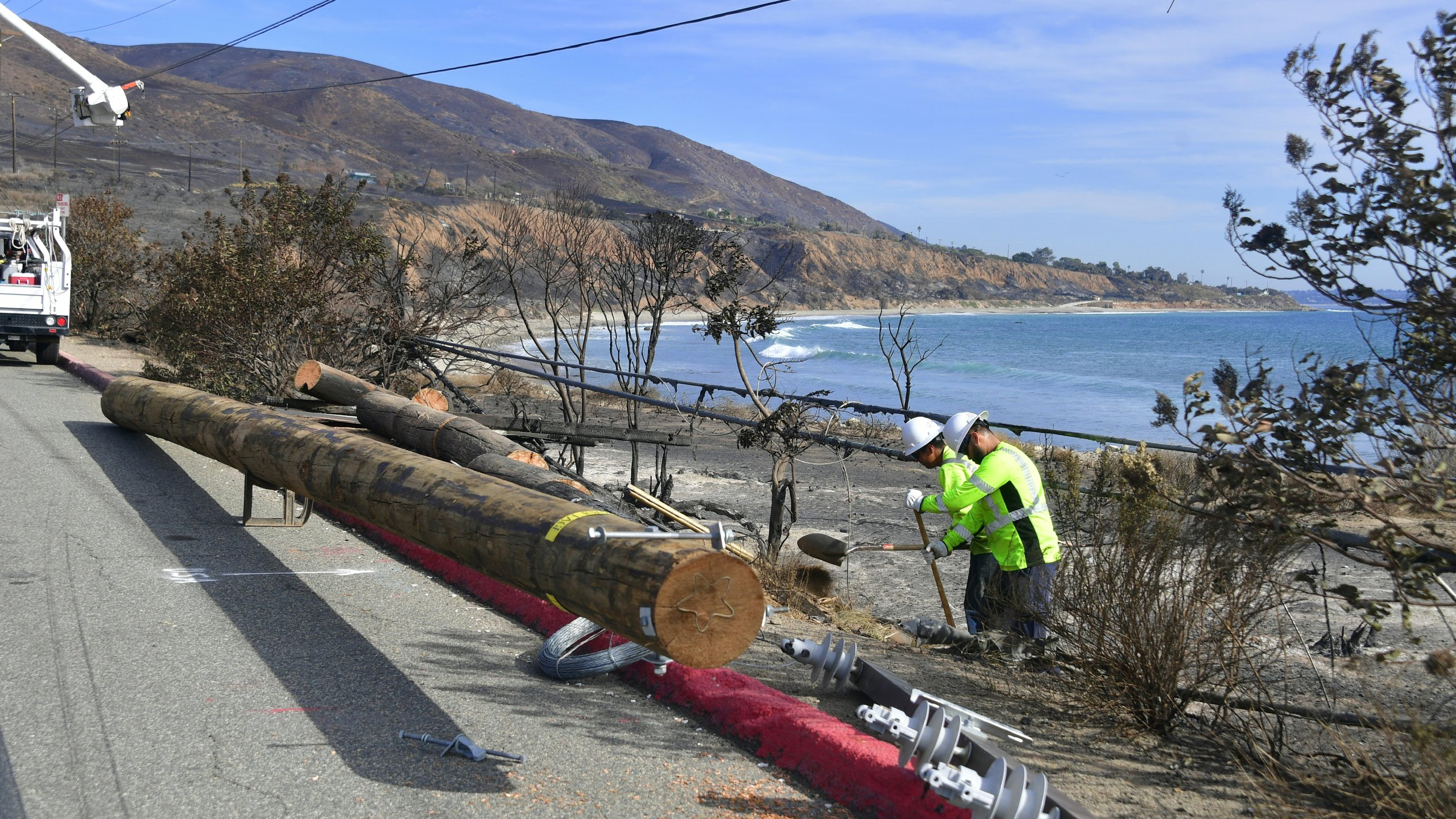Contract workers help repair downed power lines along the Pacific Coast Highway in Malibu on Nov. 15, 2018. (Credit: Frederic J. Brown / AFP / Getty Images)