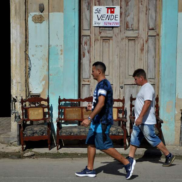 """Men pass by a house with a sign reading """"For Sale"""" in Havana, on Dec. 3, 2018. (Credit: YAMIL LAGE/AFP/Getty Images)"""