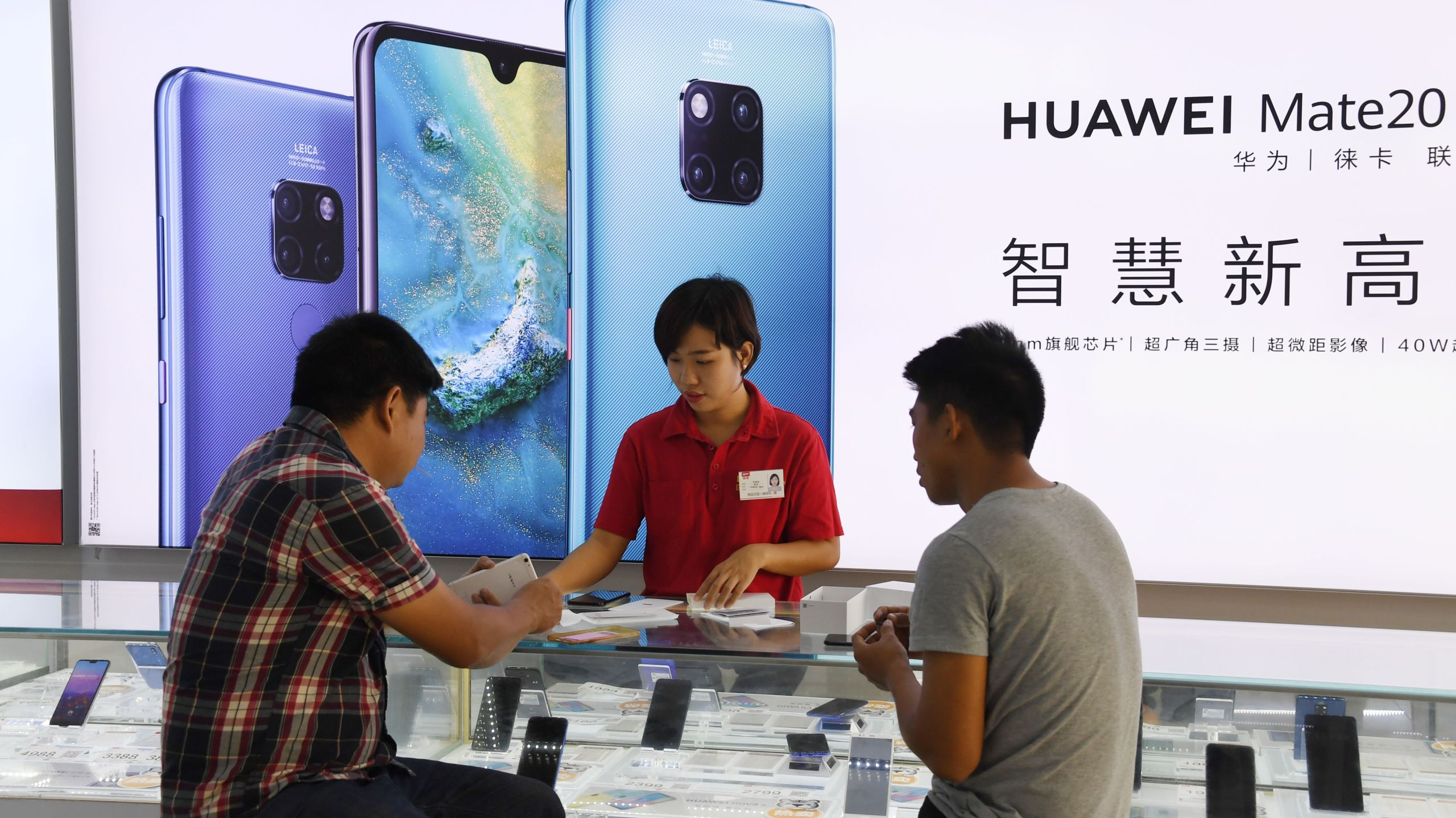 Customers are served at a Huawei stand in a store in Sanya on China's tropical Hainan Island on December 8, 2018.(Credit: Greg Baker/AFPGetty Images)