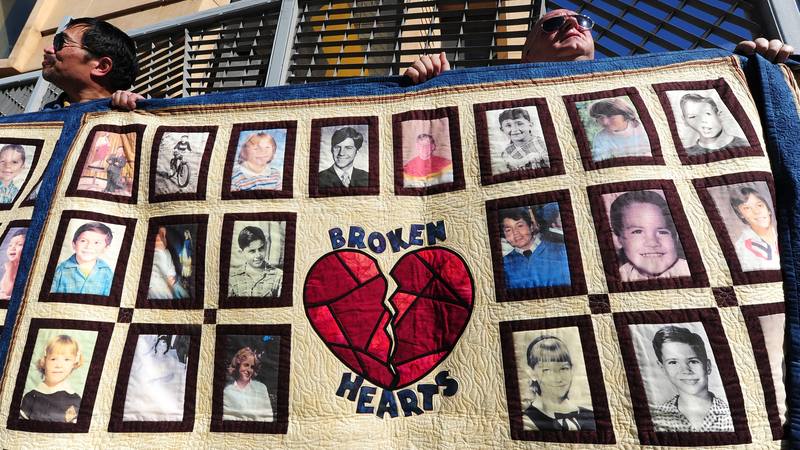 Abuse victim Jorgen Olsen, right, and supporter Glenn Gorospa, left, hold quilts bearing portraits of abused children while gathered outside the Cathedral of Our Lady of the Angels on Feb. 1, 2013. (Credit: Frederic J. Brown / AFP / Getty Images)