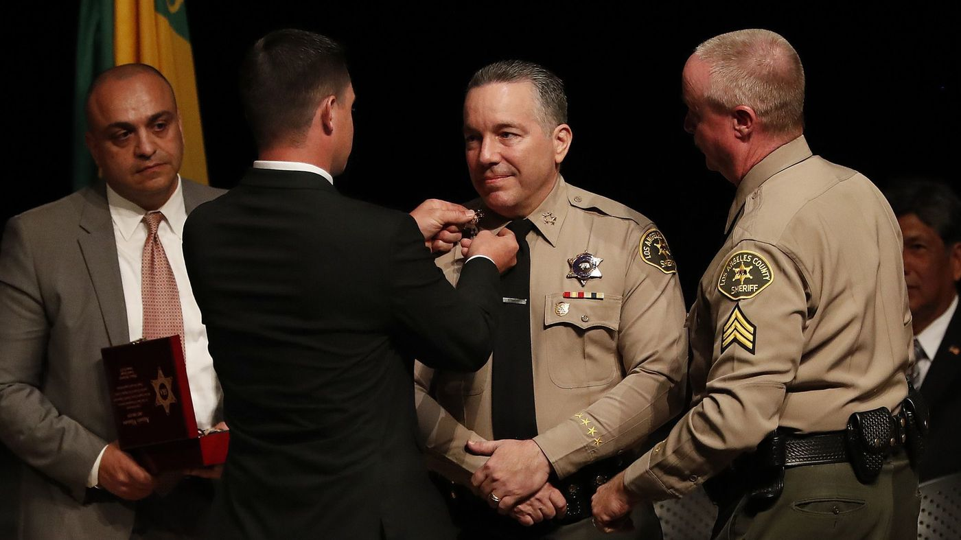 Jared Villanueva places a pin on the collar of his father, Alex Villanueva, at his swearing-in as Los Angeles County sheriff on Dec. 3, 2018. (Credit: Mel Melcon / Los Angeles Times)