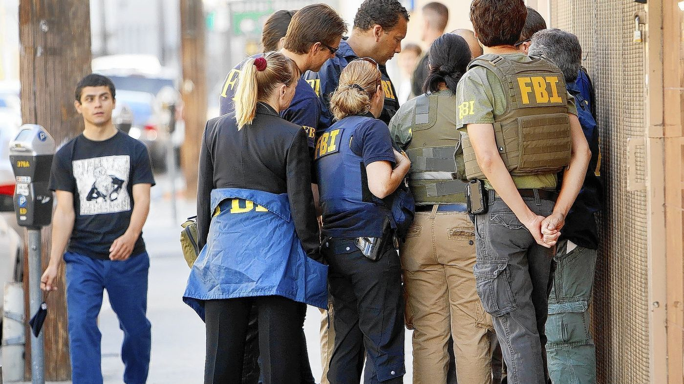 In this undated photo, FBI agents huddle in the 700 block of East Pico Boulevard as a series of raids are carried out in downtown L.A.'s Fashion District. (Credit: Al Seib, Los Angeles Times)
