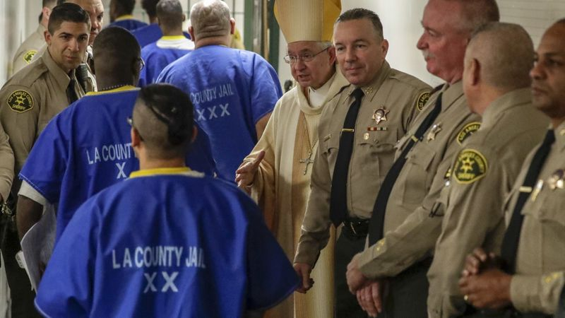 Archbishop Jose H. Gomez, center, and L.A. County Sheriff Alex Villanueva, fourth from right, greet inmates after a Christmas Mass at Men's Central Jail on Dec. 25, 2018. (Irfan Khan / Los Angeles Times)