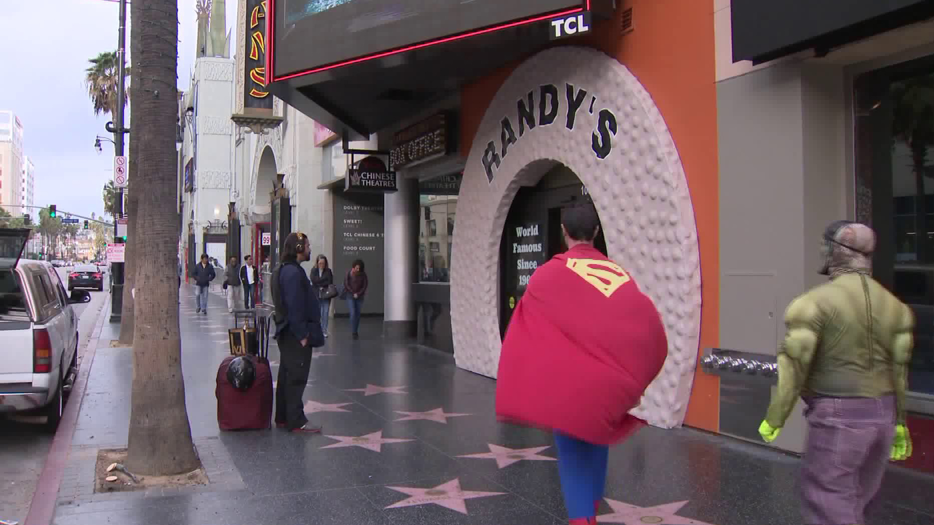 Two people dressed as Superman and the Hulk walk by Randy's Donuts in Hollywood on Dec. 10, 2018. (Credit: KTLA)