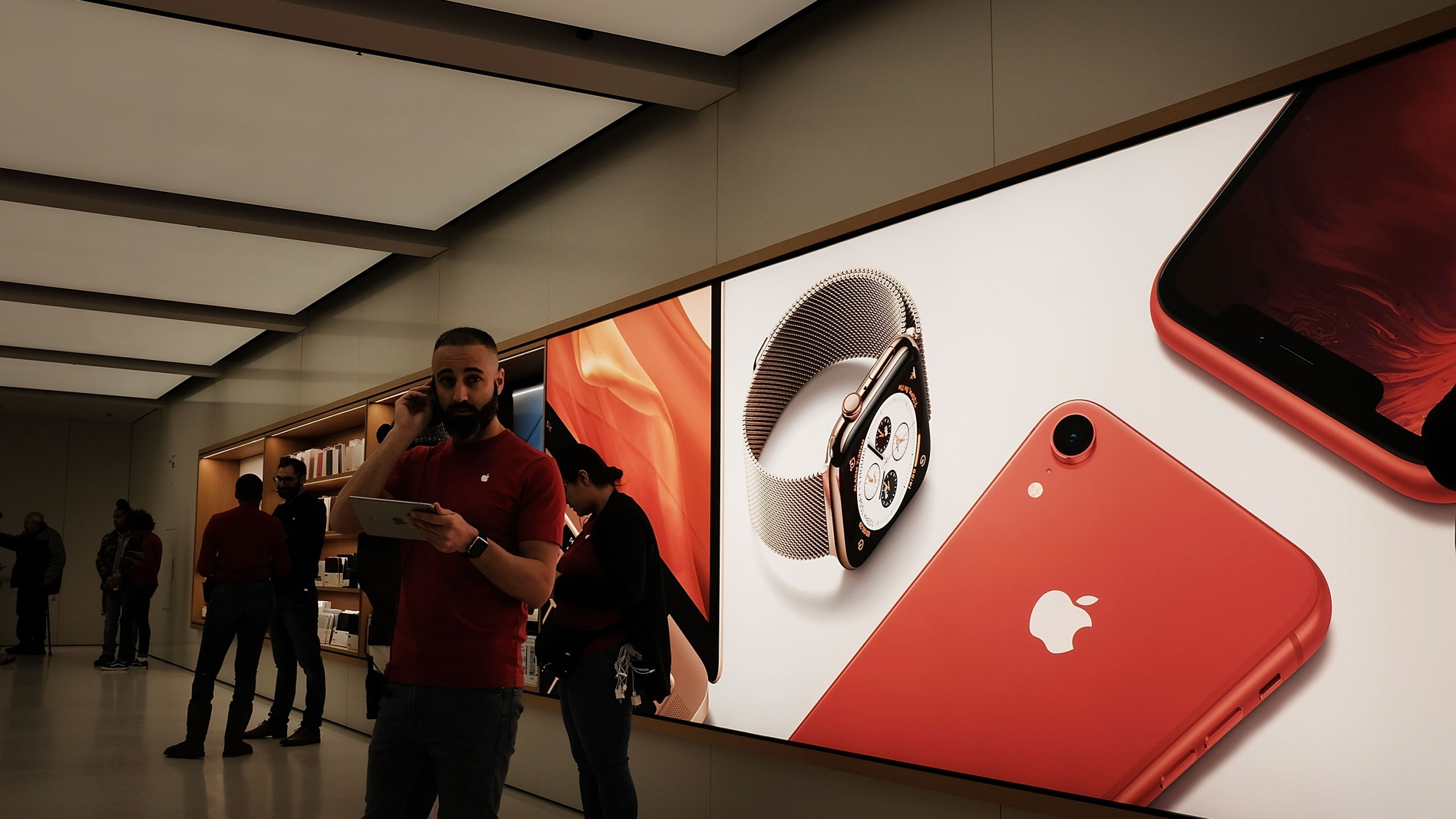 People stand in an Apple store in lower Manhattan on Nov. 20, 2018 in New York City. (Credit: Spencer Platt/Getty Images)
