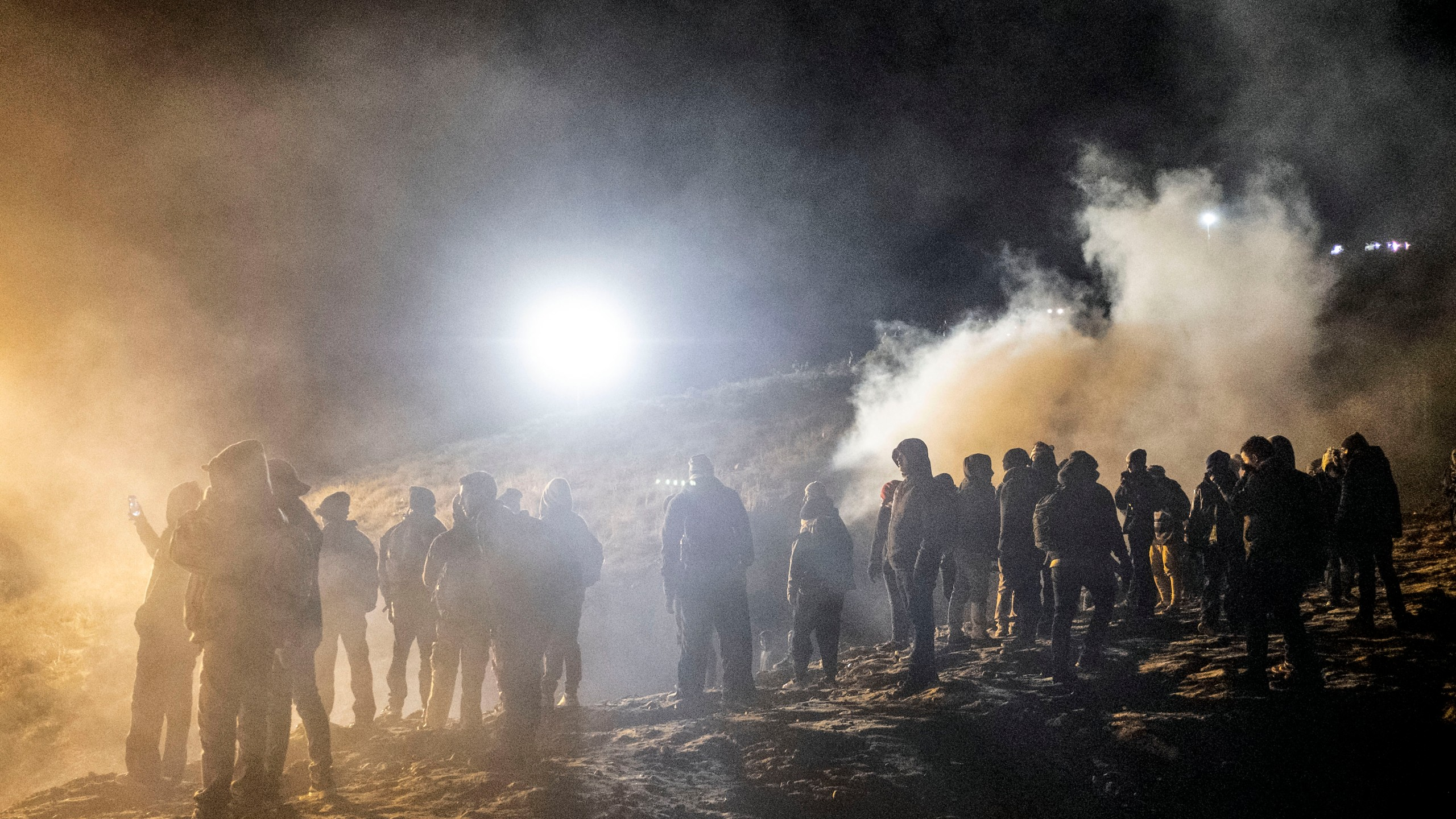 Central American migrants stand amid a cloud of tear gas thrown by the US border patrol, after they tried to cross from Tijuana to San Diego in the US, as seen from Tijuana, Baja California state, Mexico on January 1, 2019. (Credit: GUILLERMO ARIAS/AFP/Getty Images)