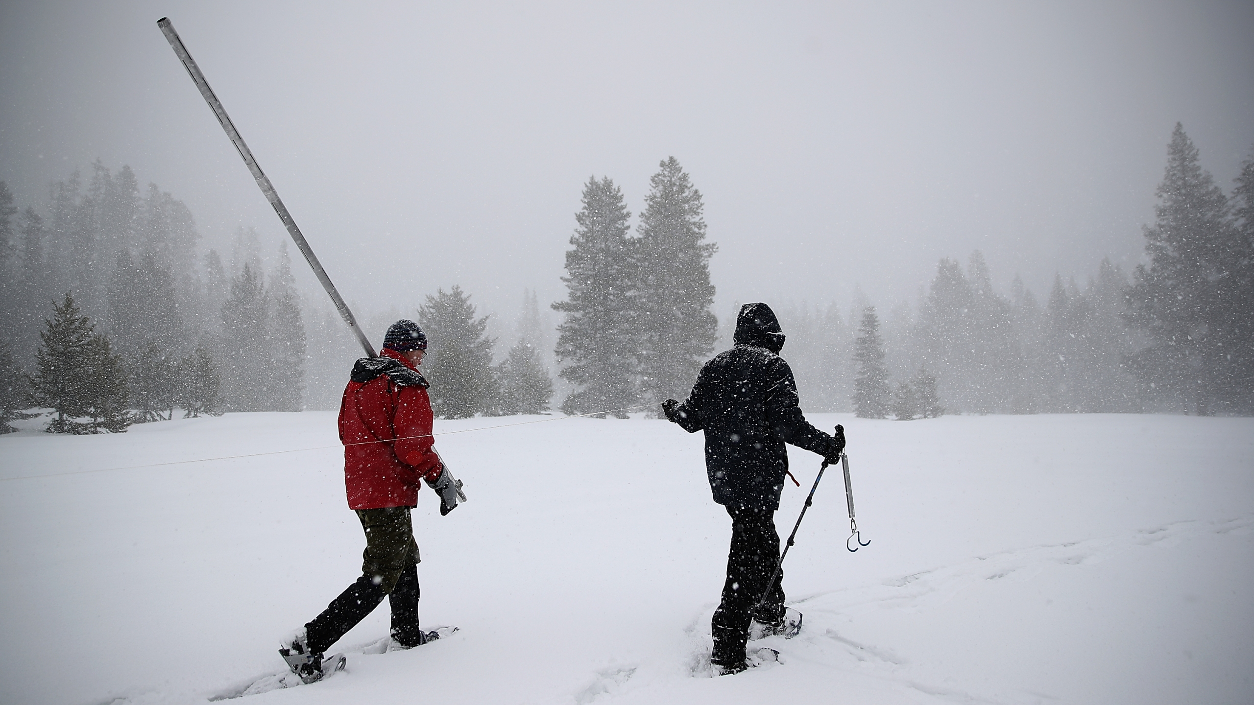 Nic Enstice, right, and Frank Gehrke, left, Chief of the California Cooperative Snow Surveys Program for the Department of Water Resources, walk through a snow covered field to take a sample of the Sierra snowpack on March 30, 2017 near Twin Bridges. (Credit: Justin Sullivan/Getty Images)