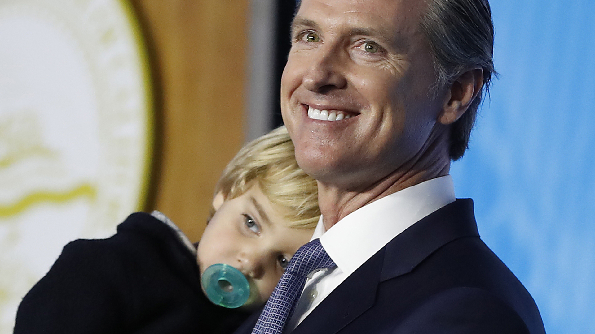 Gov. Gavin Newsom carries his 2-year-old son Dutch while delivering his inaugural address after being sworn in as the 40th governor of California on Jan. 7, 2019, in Sacramento. (Credit: Stephen Lam/Getty Images)