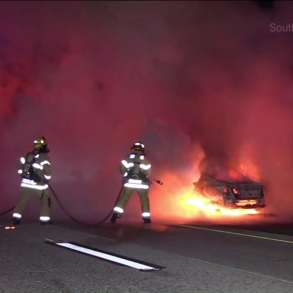 A car burst into flames after the driver hit the center divider while driving the wrong way on the 91 Freeway. (Credit: Southern Counties News)