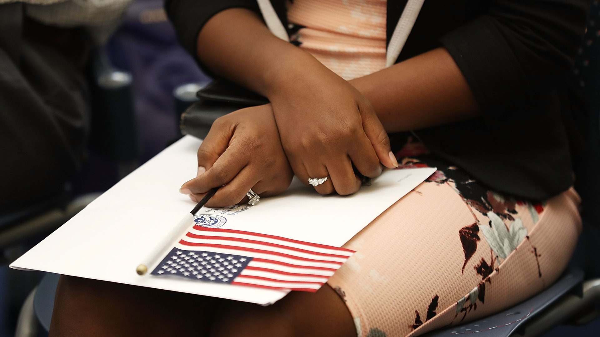 A woman holds an American flag during a ceremony to become an American citizen during a U.S. Citizenship and Immigration Services naturalization ceremony at the Miami field Office on Aug. 17, 2018, in Miami, Florida. (Credit: Joe Raedle/Getty Images)