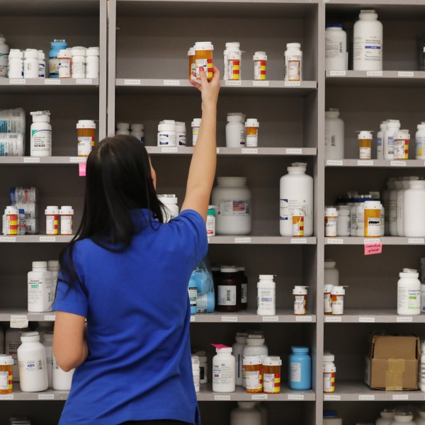 A pharmacy technician grabs a bottle of medication off a shelf on Sept. 10, 2018 in Midvale, Utah. (Credit: George Frey/Getty Images)