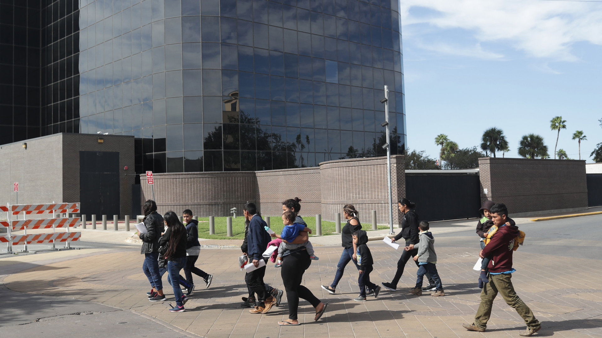 Immigrant asylum seekers walk past a U.S. federal courthouse after being released by U.S. Customs and Border Protection on Nov. 1, 2018 in McAllen, Texas. (Credit: John Moore/Getty Images)