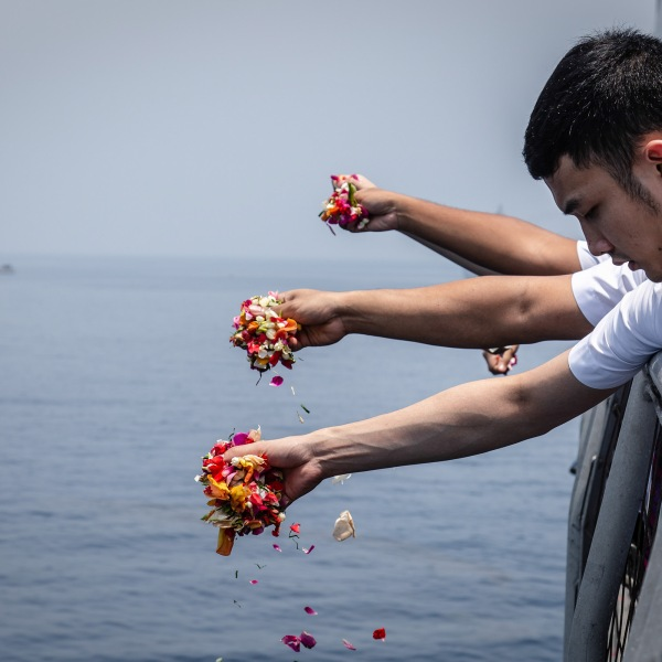 Colleagues of victims of Lion Air flight JT 610 throw flowers on deck of the Indonesian Navy ship KRI Banjarmasin during a visit to the crash site on November 6, 2018 in Karawang, Indonesia. (Credit: Ulet Ifansasti/Getty Images)